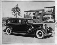 1934 Packard sedan, seven-eights right side view, couple seated in back, male driver
