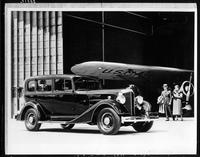 1934 Packard sedan with U.S. mail plane at airplane hangar