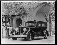 1934 Packard sedan, three-quarter front left view, couple standing at front right side