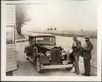 1934 Packard coupe, three-quarter front view, two men standing at driver's side