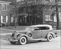 1935 Packard phaeton, three-quarter left side view, top raised, parked on street