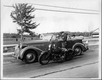 1935 Packard touring car being pulled over by a motorcycle policeman