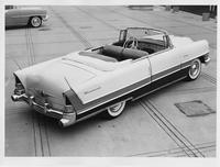 1955 Packard convertible, three-quarter rear right elevation view, top folded, parked in driveway