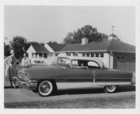 1956 Packard sedan, woman behind wheel, two women standing at front of car