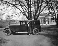 Mrs. Mabel S. Douglas, dean of New Jersey College for Women, standing in passenger doorway of her 1927 Packard sedan