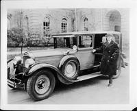Glenn Frank, president of the University of Wisconsin, standing in passenger doorway of his 1928 Packard sedan limousine