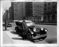 Symphony conductor, Dr. Walter Damrosch, standing at front of his 1930 Packard phaeton
