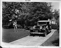 Dick Powell standing on lawn near driveway with his 1932 Packard convertible victoria