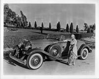 Madge Evans with golf clubs next to her 1932 Packard coupe roadster