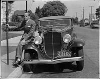 Al Jolson sitting on front passenger side fender of his 1932 Packard coupe roadster