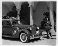Film star Harold Lloyd standing next to his 1935 Packard sedan