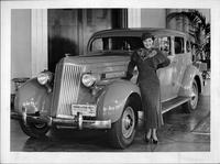 Miss Jean Parker standing by front driver fender of 1935 Packard sedan in Packard dealer showroom