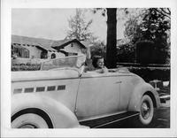 Dixie Dunbar waving, behind wheel of 1936 Packard convertible coupe
