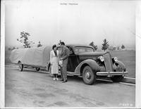 Mady Correll and Harvey Stephens next to 1936 Packard sedan with a trailer hitched to back