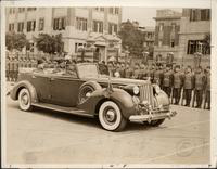 King Faruk I of Egypt inspecting his troops in the royal palace convertible, a 1939 Packard convertible sedan
