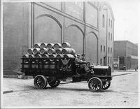 An early 1900s Packard truck used by Goebel Brewing Co., parked on street, full of wooden beer barrels, two men in seat