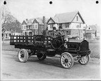 An early 1900s Packard truck, right side view, parked on residential street houses in background, two men in seat