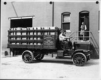 An early 1900s Packard truck, right side view, parked on street next to brick building, full of wooden crates, two men in seat