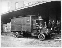 An early 1900s Packard truck, right side view, parked at loading dock, man behind wheel, four men standing next to truck