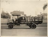 An early 1900s Packard truck, left side view, parked on street houses in background, man behind wheel