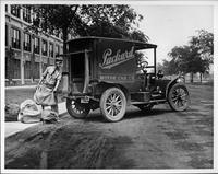 1910 Packard truck, three-quarter rear left view, parked on road, man loading mail into back of truck