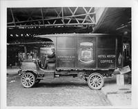 1911-12 Packard truck, left side view, man in driver seat, parked in loading area