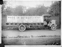1915 Packard truck, right side view, parked on street, man behind wheel