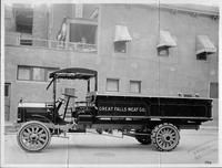1915 Packard truck, left side view, parked on street next to building