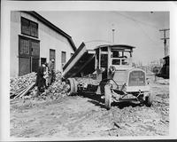 1917 Packard dump truck, three-quarter front view, dumping out a load of bricks