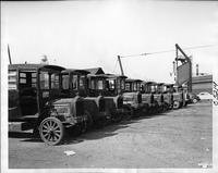 Line up of eleven 1921-23 Packard trucks, parked in yard