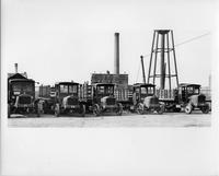 Line up of five 1921-23 Packard trucks, parked in yard, front view