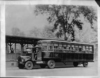 1922 Packard truck with City of Detroit bus trailer, two men in front cab, passengers in back