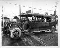 1915-16 Packard jitney bus, seven-eights left side view, parked on street, man behind wheel, two male passengers