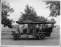1910 Packard jitney bus, left side view, parked on street