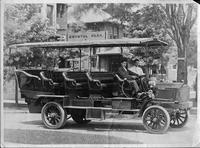 1910 Packard jitney bus used at Crystal Park, right side view, parked on street, two men in front seat