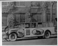 Packard bus, belonging to U.S. Silver Fox Farms, parked on street, in front of Packard administration building