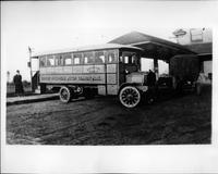 Packard bus, nine-tenths left side view, parked on street, coach in background