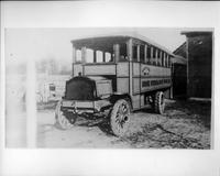 Packard bus, three-quarter front view, parked on road