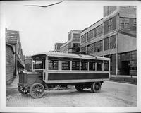 Packard electric bus, right side view, parked on brick-paved street