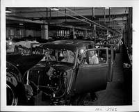 Packard factory assembly line, workers inside bodies installing interior parts