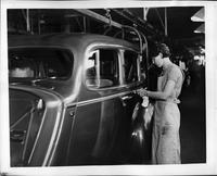 Female automobile worker applying body striping on Packard assembly line, 1936