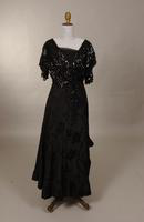Evening gown of black silk with scroll-leaf brocade pattern from the early twentieth century