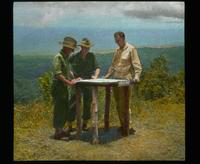 "Dennis Cooper (right) and Two Air Force Soldiers Looking at ""Area Map"""