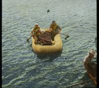 Two Men Moving an Injured Man in Raft to Receive Care