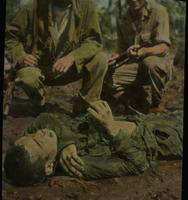 Two American Soldiers Looking at a Dead Soldier