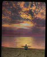 View of a Man Sitting on Beach at Sunset