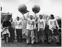Football players hold balloons in front of a homecoming float.