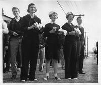 Young women in sailor outfits enjoy refreshments at a homecoming event.