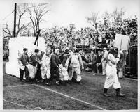 A float is pulled by people in overalls while the stands behind them are filled.