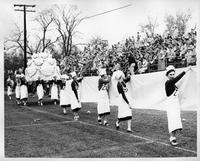 A float resembling a wedding cake is carried by the Zeta Chi sorority.